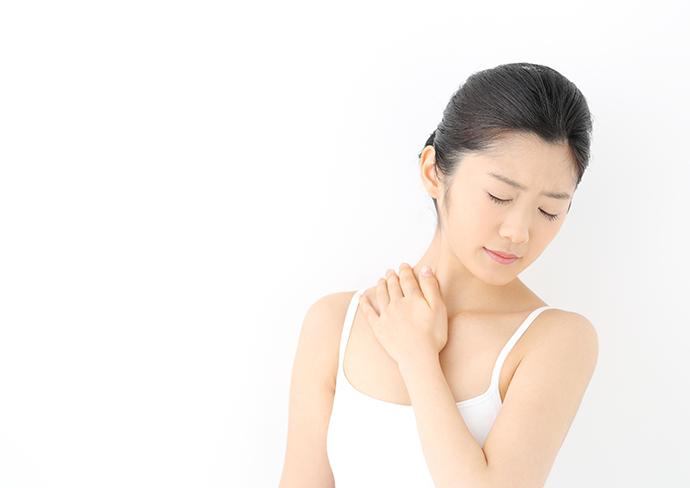 首の付け根を抑える女性